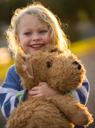 close up of a cute smiling 4 year old caucasian child hugging his big brown teddy bear backlit by the setting sun Stock Photo
