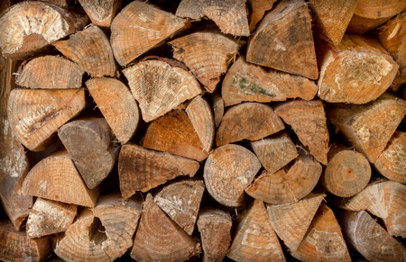 no fires: close up of chopped pine firewood logs stacked against a wall seen front on