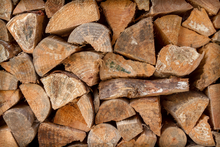 close up of chopped pine firewood logs stacked against a wall seen front on