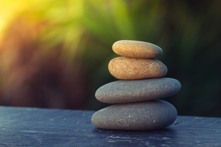 pile of smooth round pebbles balanced on top of  an old plank,  with an out of focus background for copy space and sun flare coming from the top left corner. Stock Photo