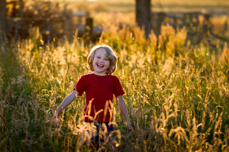 old photograph: cute blonde haired  5 year old caucasian boy standing in a field at sunset being backlit by the setting sun. Stock Photo