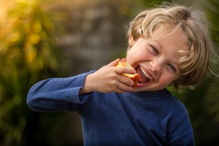 A blonde haired 5 year old child eating an apple and smiling at sunset Stock Photo