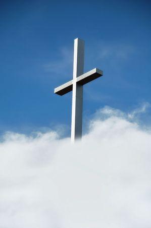 pentimento: traversa cristiana dacciaio contro il cielo blu e le nubi Archivio Fotografico