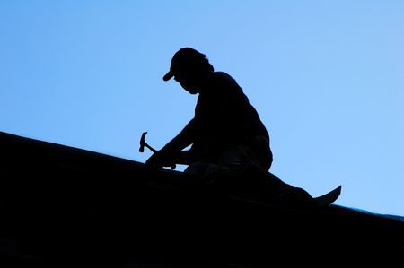 man on roof with hammer