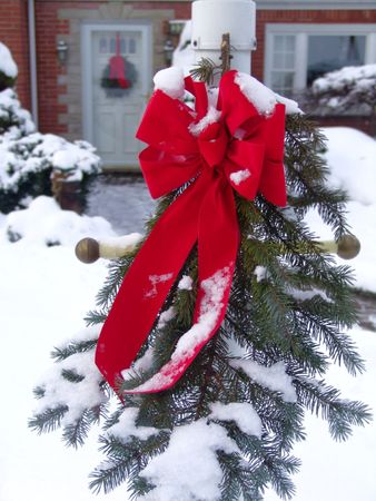 Christmas wreath in front of house in snow