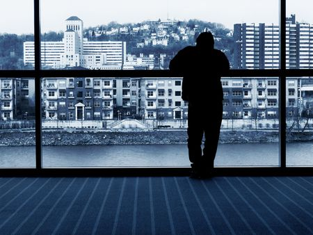 man waiting - looking out window at city buildings and river