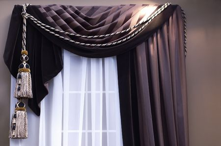 brown swag curtains with tassels on window with sheers Фото со стока - 339410