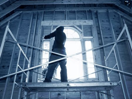 men installing arched window at top of cathedral ceiling