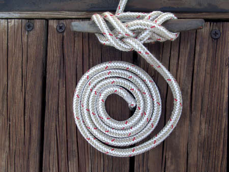 coiled rope: white boaters rope artistically coiled and attached to cleat on dock