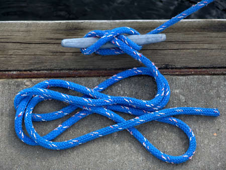 cleat: blue boaters rope attached to cleat on dock