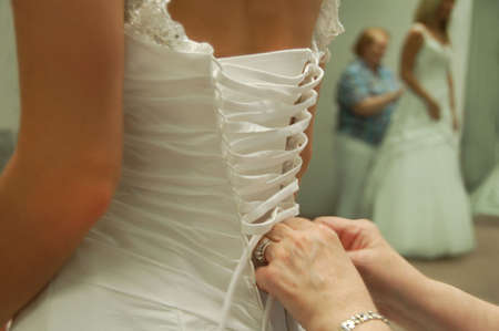 woman getting ready for her wedding day with help lacing her gown