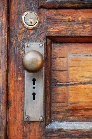 antique door knob on old wooden door with panels photo