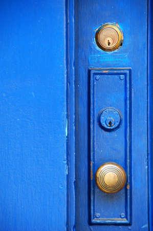 door knob: old door knob on blue door with bolt lock Stock Photo