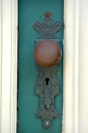 very old doorknob painted green with white panels