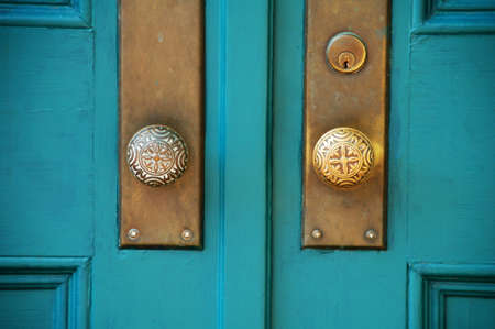 entrance door: old double wooden doors with brass hardware