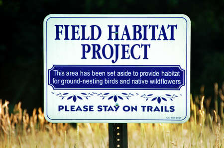 a field habitat project sign to protect ground-nesting birds and native wildflowers