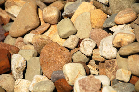 layer of different colored stones and rocks in sunlight