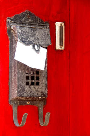 rusty antique mailbox hanging on red painted wall of residence Stock Photo