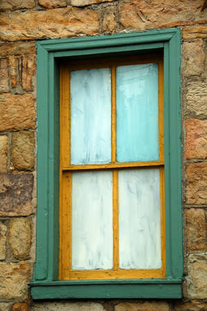 the panes are painted on an old window with green trim on a stone house