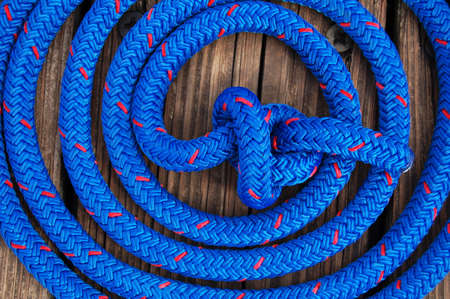 blue and red speckled nautical rope coiled and knotted securing boat to dock Stock Photo
