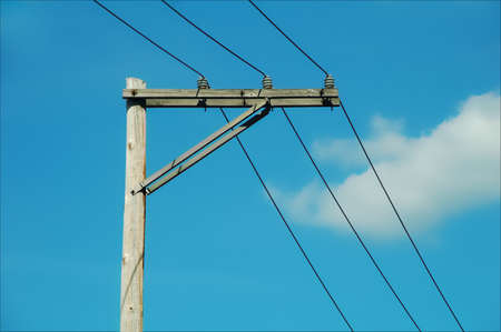 Utility lines on wooden pole against blue sky