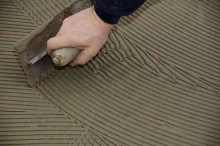 man hand troweling adhesive for ceramic tile flooring