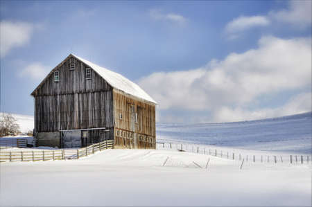 view of a solitary barn in snow against blue sky