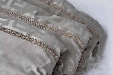 three decorative beige pillows with tassels