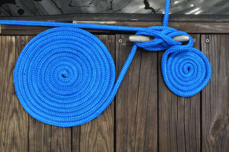 two rolls of blue cord rope securing boat to dock Stock Photo
