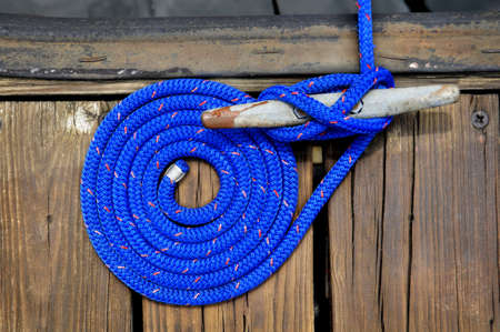 coiled blue rope securing boat to wooden dock
