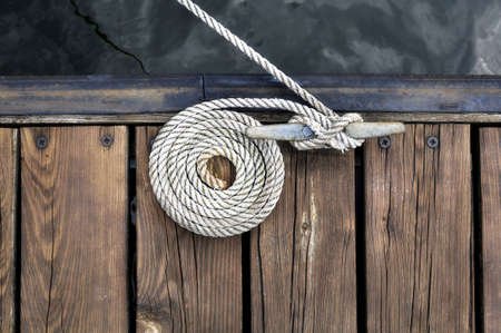 pier: curled white rope securing boat to wooden dock