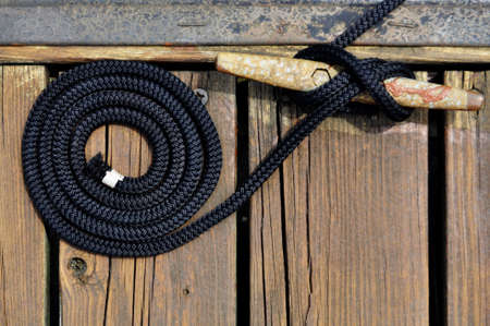 black rope securing boat to wooden dock