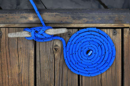 blue boat rope rolled in a circle securing boat to wooden dock