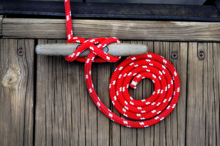 red boat rope curled in a circle securing boat to wooden dock Stock Photo
