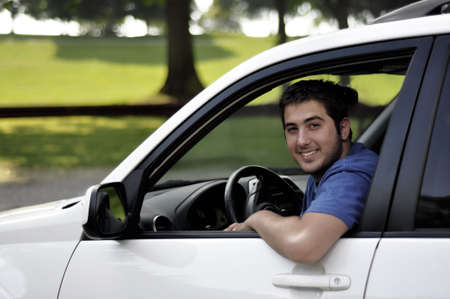 young man sitting at the wheel of a white car