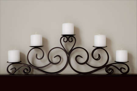 five white candles on a black metal decorative stand