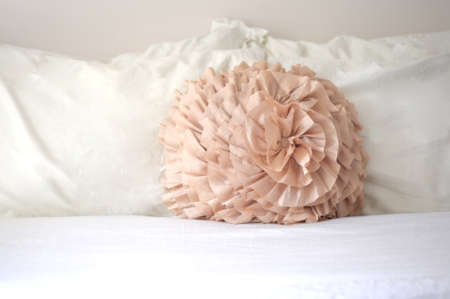 Pastel peach decorative pillow on white sheets in bedroom Stock Photo