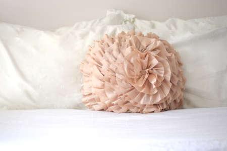 Pastel peach decorative pillow on white sheets in bedroom Reklamní fotografie