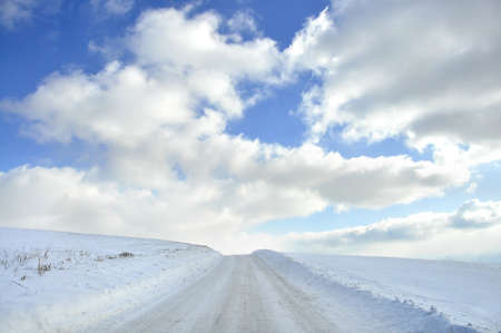 Snow covered isolated country road with beautiful clouds and blue sky Stock Photo