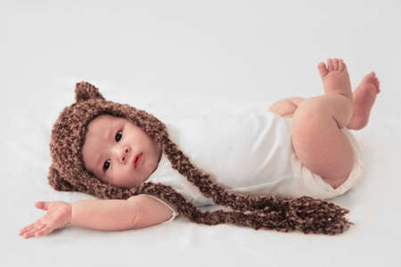 cute infant boy in white with knitted bear hat photo