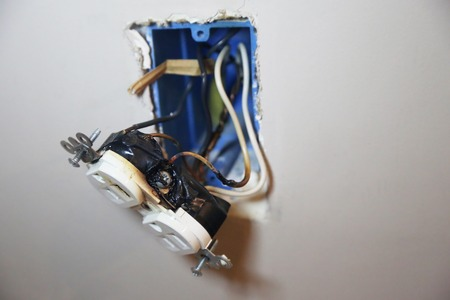 Wall outlet with burned wires and melted plastic
