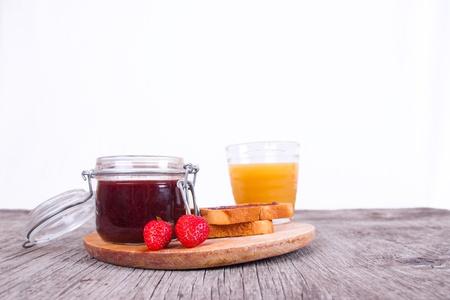 Crispbread, strawberry jam, butter and peach juice for breakfast