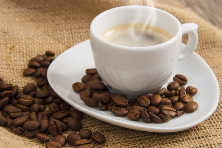Cup of hot espresso coffee on jute vintage background
