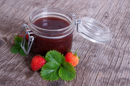 Jar of strawberry jam on rustic wood background with leaves and fruits Stock Photo - 18953673