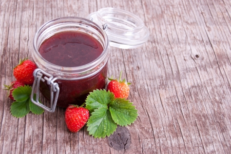 Jar of strawberry jam on rustic wood background with leaves and fruits