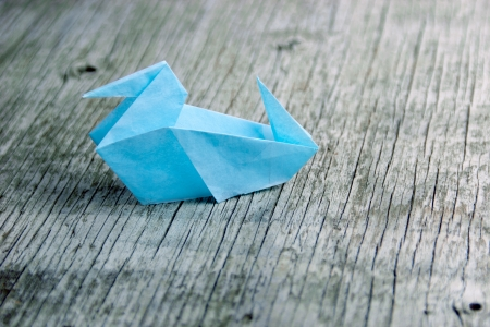 Blue Origami duck on vintage wood background