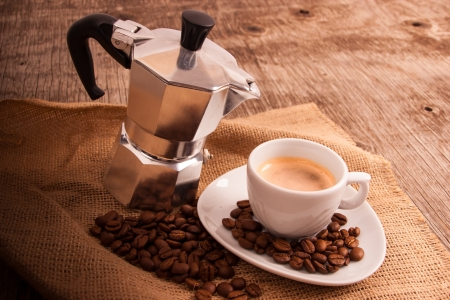 Cup of hot espresso coffee on jute vintage background and espresso pot Stock Photo