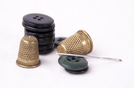 taylor:  Thimble with needle and buttons isolated on white background