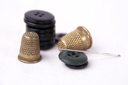 Thimble with needle and buttons isolated on white background