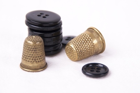 Thimble with needle and buttons isolated on white background Stock Photo